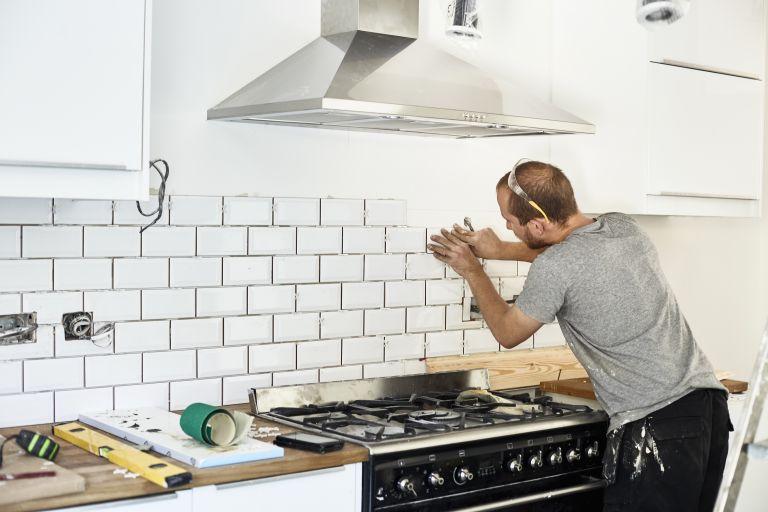 man putting up a subway tile backsplash