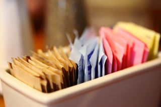 Close-Up Of Sugar And Sweetener Packets In Container At Cafe.