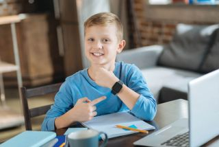 Delighted boy smiles while pointing at his smartwatch