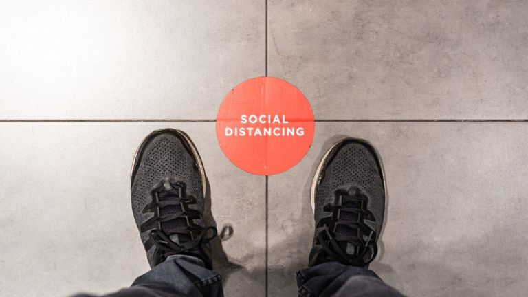 Standing at the social distancing marking sticker - stock photo