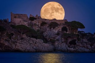Full moon over the old castle in Costa Brava in a holiday village Fosca , Spain.