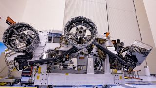 Three of the six flight wheels that will travel to Mars can be seen attached to NASA's Perseverance rover (which is inverted on a handling fixture) on March 30, 2020 at the Kennedy Space Center in Florida. The protective antistatic foil covering the wheels will be removed before launch this summer.