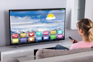 Woman watching large-screen smart TV displaying temperature in Berlin.