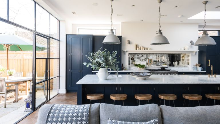 Open plan kitchen ideas featuring blue cabinetry and pendant lights over a marble island.