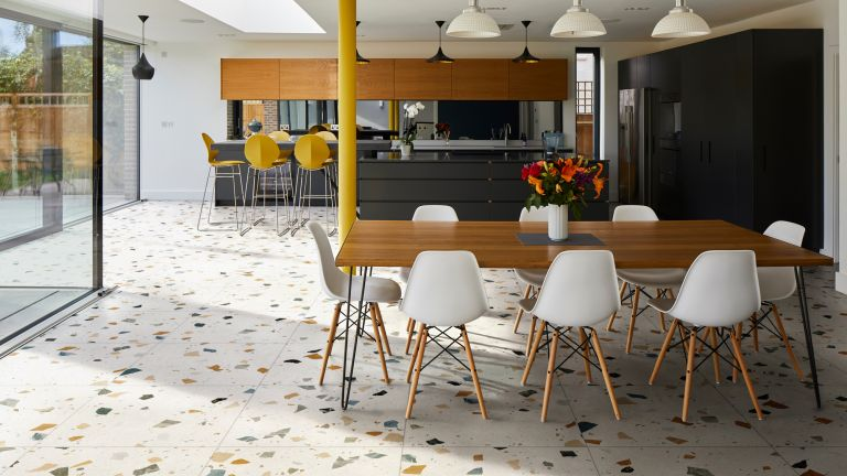 Kitchen floor tile ideas in a kitchen with terrazzo floor tiles and warm wooden and black cabinetry.