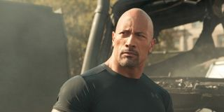Luke Hobbs (Dwayne 'The Rock' Johnson) stands in front of a burnt out vehicle in 'Fast & Furious Supercharged'