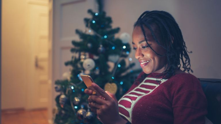 woman lookin at phone next to christmas tree