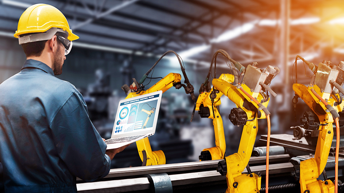 Man standing in front of manufacturing machinery with laptop