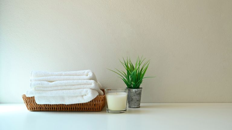 Towels folded with a candle and house plant: Bed Bath & Beyond Cyber Monday