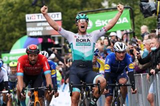 SCHWERIN GERMANY AUGUST 26 Pascal Ackermann of Germany and Team Bora Hansgrohe celebrates at finish line as stage winner ahead of Marco Haller of Austria and Team Bahrain Victorious L and Yves Lampaert of Belgium and Team Deceuninck QuickStep R during the 35th Deutschland Tour 2021 Stage 1 a 191km stage from Stralsund to Schwerin DeineTour on August 26 2021 in Schwerin Germany Photo by Christian KasparBartkeGetty Images